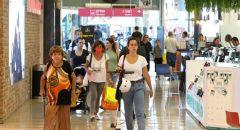 المتسوقون يتجولون في المجمعات التجارية في البلاد - بدون كمامات لاول مرة منذ اكثر من عام